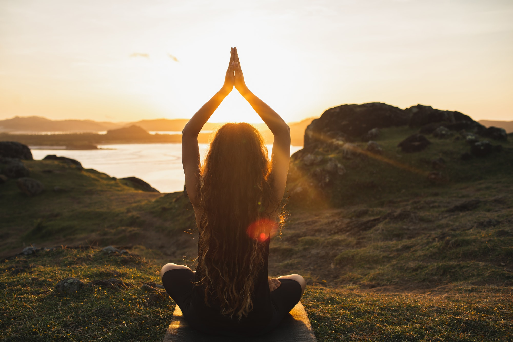 Young woman practicing yoga outdoors. Spiritual harmony, introspection and well-being concept